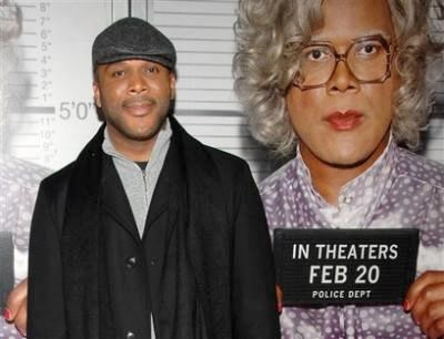 Tyler Perry in front of 'Madea Goes To Jail' poster