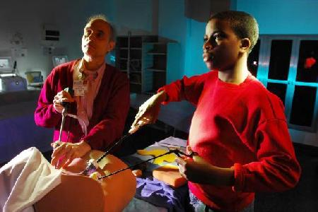 14-year-old Tony Hansberry II shown working with Bruce Nappi, the administrative director at the University of Florida's simulation center at its Jacksonville medical campus, on a new technique for sewing up hysterectomy patients. Photo by JON M. FLETCHER/The Times-Union
