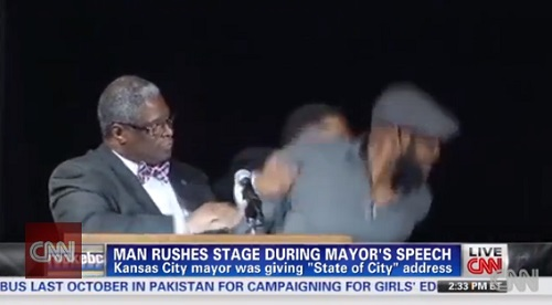Kansas City Mayor Sly James' security team grabbed an unidentified man from the stage.