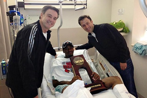 Coach Rick Pitino and former Assistant Coach Richard Pitino, visit Kevin Ware right after his 2-hour surgery Sunday on his right leg to present him with the Midwest Regional championship trophy.