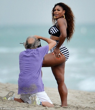 Serena Williams being captured in a black and white striped swimsuit on a beach in Miami, Florida.