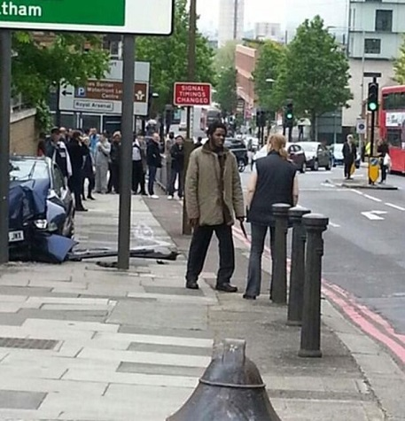 The other man responsible for the vicious attack against a british soldier in broad daylight stands and talks with a woman after killing the man.