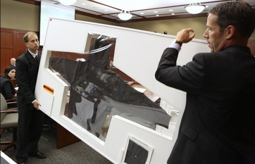 State's attorneys hold the hoodie up, encased in glass, for display during George Zimmerman murder trial.