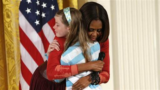 First Lady Michelle Obama hugs Charlotte Bell, 10, who gave the first lady her father's resume and said he had been out of work for three years