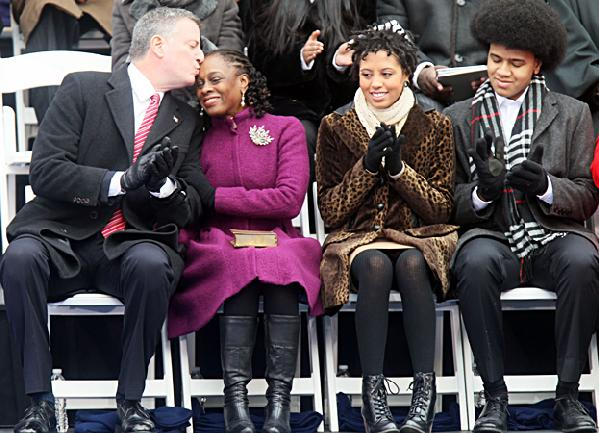 (L-R) New york City Mayor Bill de Blasio kisses wife, First Lady, Chirlane McCray, seated next to daughter Chiara and son Dante