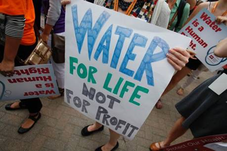 Demonstrators hold signs as they protest against the Detroit Water and Sewerage Department July 18, 2014, in Detroit. The department has disconnected water to thousands of Detroit residents who are delinquent with their bills.