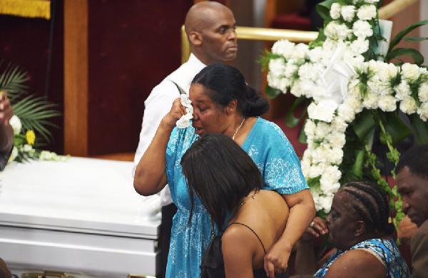 Esaw Garner, wife of Eric Garner dries her teary eyes at her husbands funeral