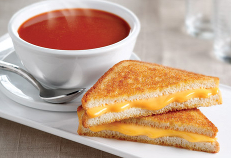 Scrumptous grilled cheese sandwich with a cup of tomato soup.