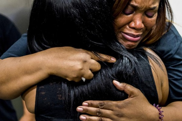 Charlene Woodward, grandmother of Ti'Airra Woodward, right, cries as she embraces a family member.