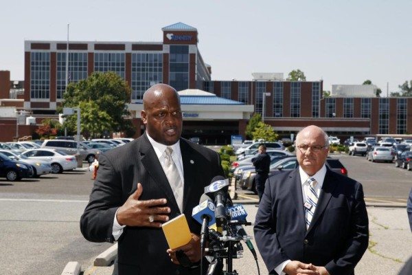 Camden County Prosecutor's Office Capt. Ron Moten, left, stands with in front of Kennedy Hospital with hospital chief of safety, David Condoluci, as he answers a question about shootings at the facility Wednesday, Aug. 27, 2014, in Stratford, N.J.