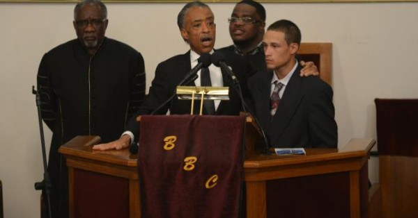 Ramsey Orta at podium with Rev. Al Sharpton at Eric Garner's funeral service