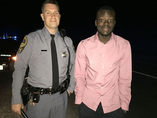Virginia State Trooper Matt Okes stands with Virginia Tech student Joseph Owusu, after helping him with a tire blowout.