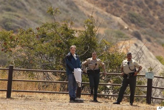 Defendant Cameron Brown, left. stands with L. A. County sheriffs deputies and jurors as a site visit is conducted.