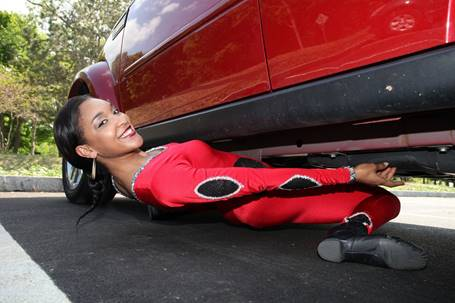 Limbo champ Shemika Charles gets down low under an SUV.