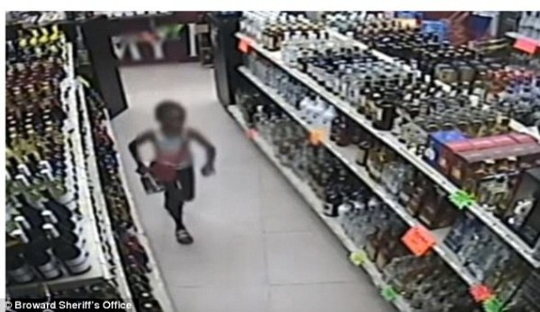 Something has spooked the little girl, so she runs back to put the Tequila back on the shelf