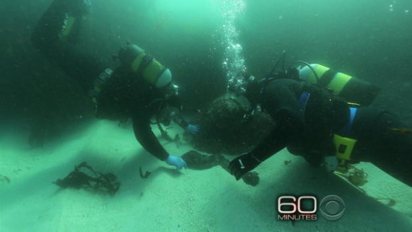 DIVERS remove artifacts from sand on sea bottom