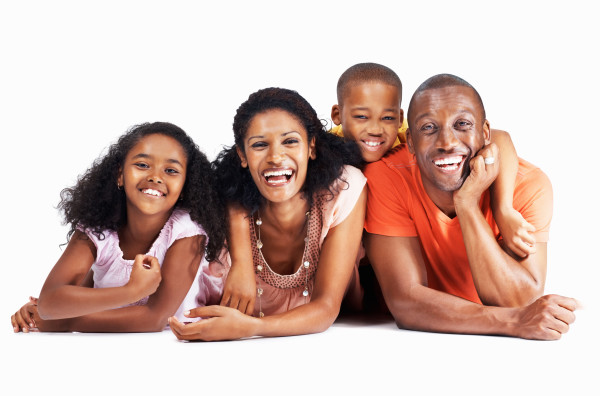 Portrait of beautiful family of four having fun while lying down over white background
