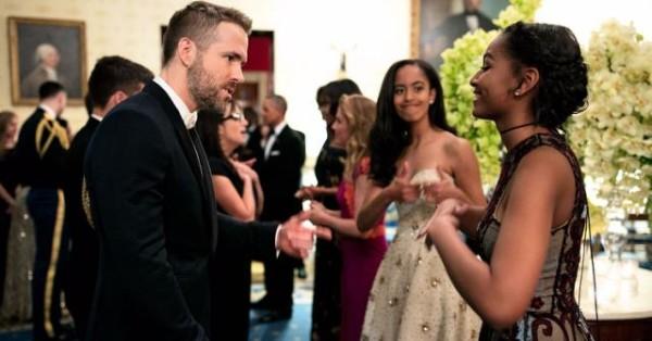 Actor Ryan Reynolds chats with Sasha Obama, while big sis Malia gives a thumbs up!