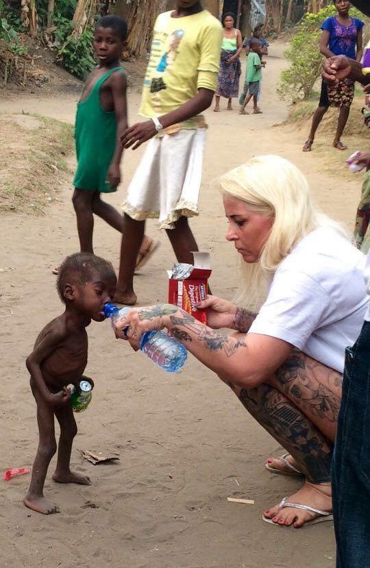 starving child being fed bottled water