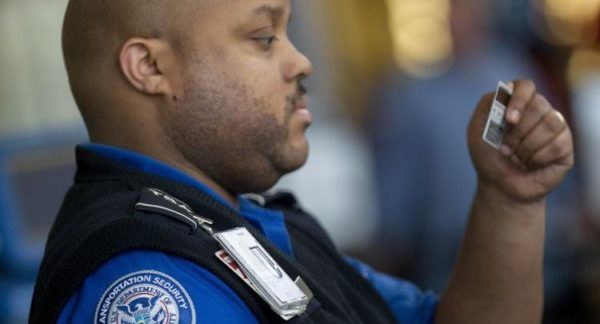 A TSA Agent studies a passenger's ID at the security checkpoint.