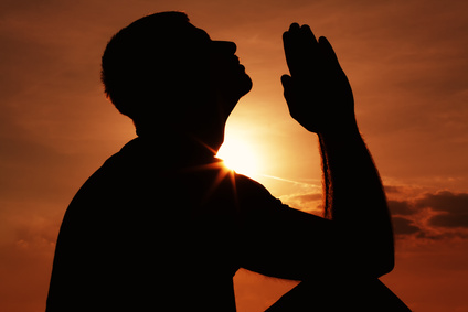 silhoutte of a praying man