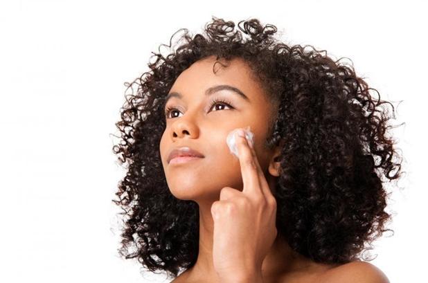 black woman (light skinned) applying make up